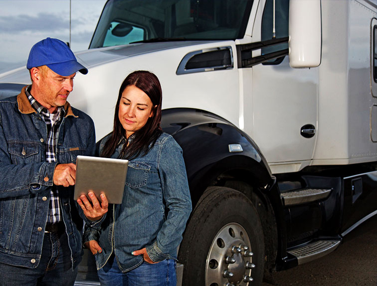 a man and a women stand next to a truck discussing something