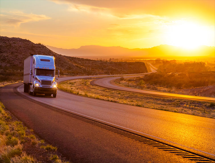 White truck on road with sunset in background