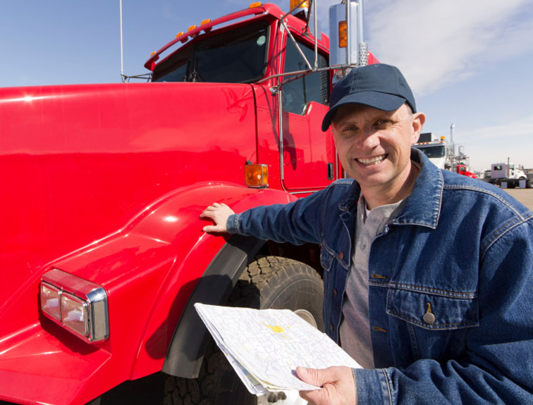 Truck driver standing with hand on semi, holding a map and smiling.