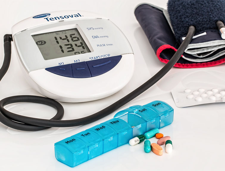 Blood pressure reader, weekly pill case, and pack of pills sitting on white table.