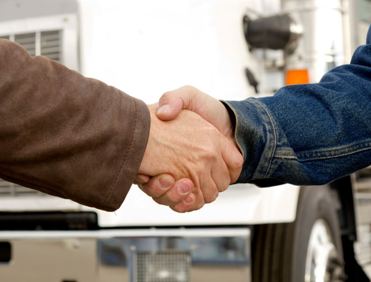 Two men shaking hands in front of a white semi