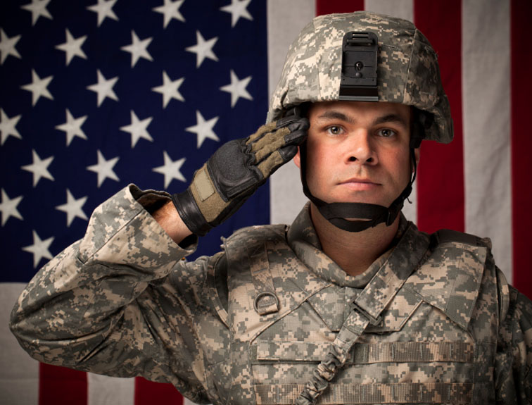 Military soldier with American flag in background.