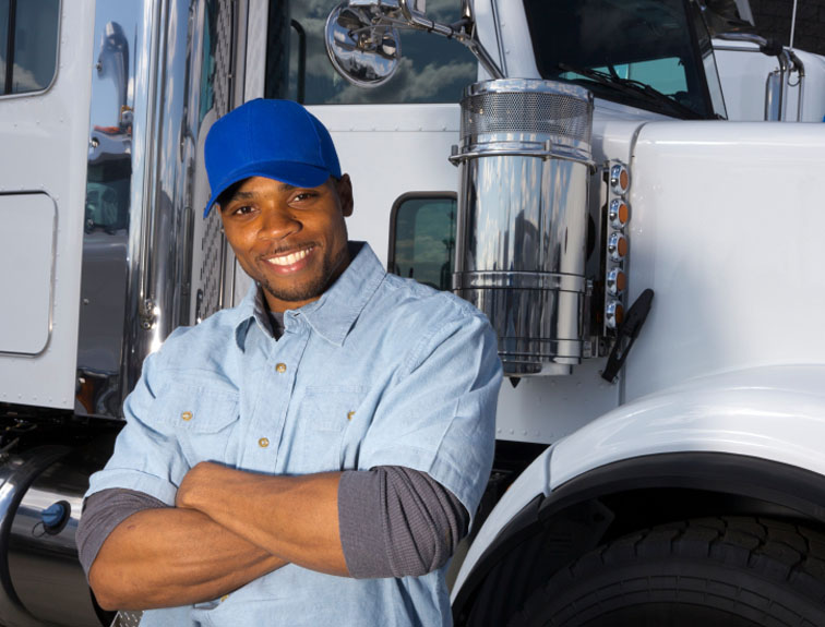 Truck driver with arms crossed leaning up against rig