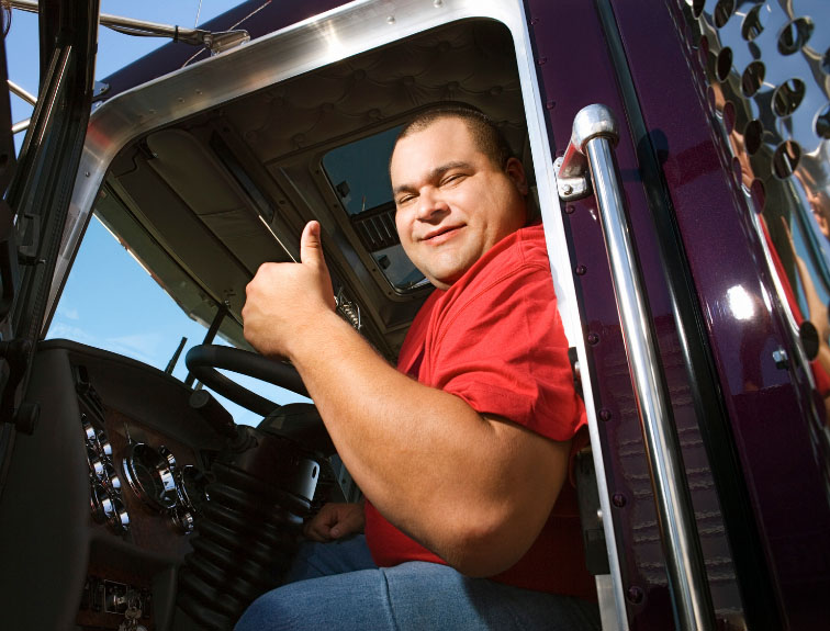 Semi driver sitting in driver seat, giving a thumbs up.