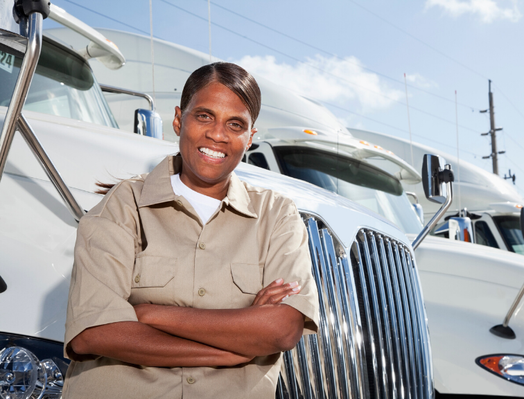 Image of African American woman trucker standing in front of CDL trucks